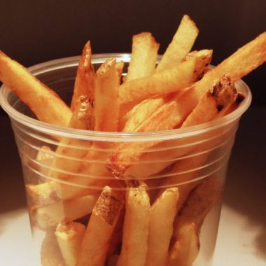 Homemade French Fries in a clear plastic cup.