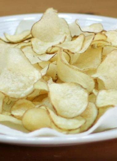 white plate with paper towel and thin crispy potato chips