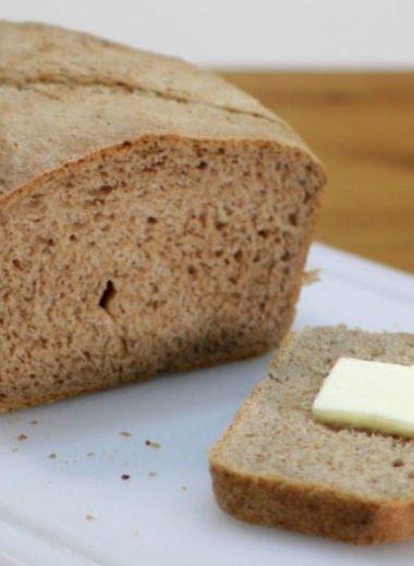 Acorn bread on white cutting board slice has butter on it