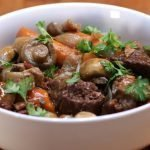A large white bowl of beef bourguignon on a wooden table