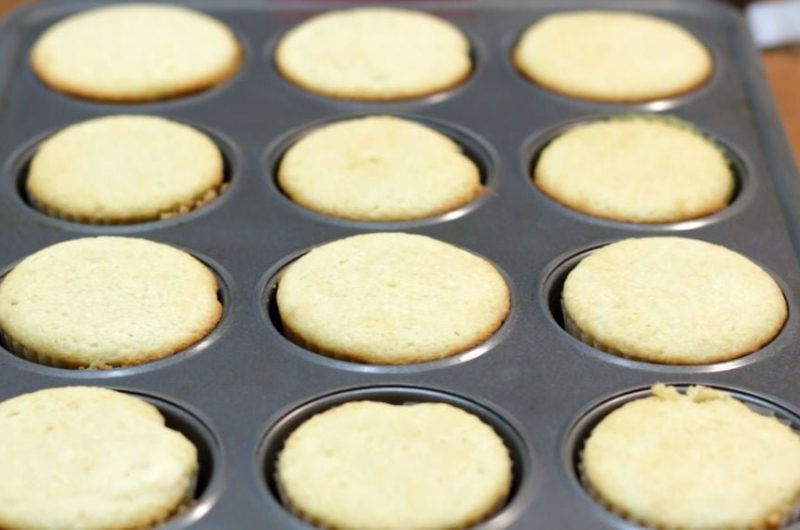 homemade vanilla cupcakes in a gray cupcake pan on wooden table
