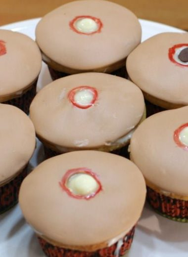 7 cupcakes with tan fondant and holes that look like pimples