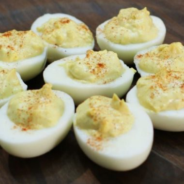 nine amazing deviled eggs on a wooden plate