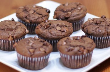 7 chocolate banana muffins on a white plate on a table
