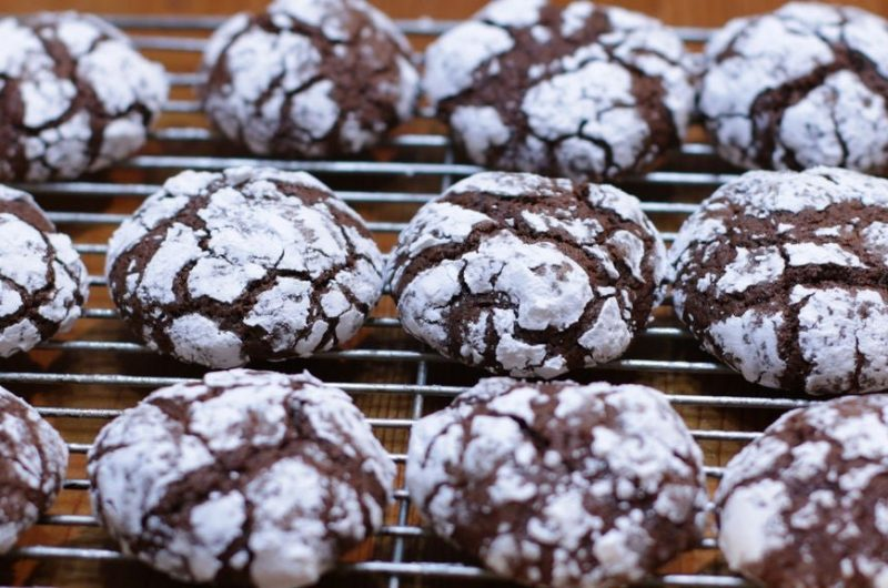 chocolate crinkles cookies on a wire rack on wooden table