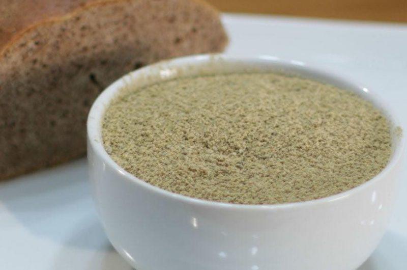 white bowl holding processed acorn flour next to acorn bread
