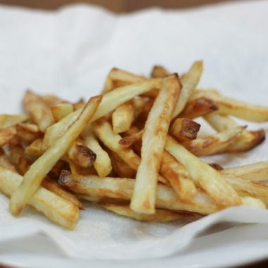 Easy crispy air fryer french fries on a white paper towel on a white plate