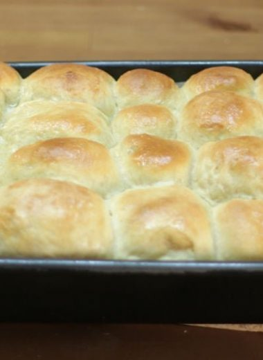 soft no knead dinner rolls in a dark gray pan on a wooden table