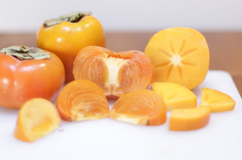 how to eat a persimmon three persimmons cut up on a white cutting board on a wooden table