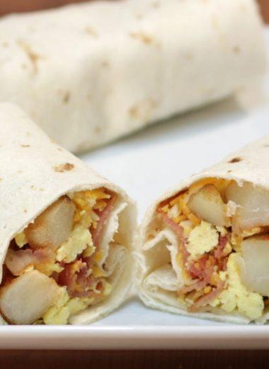 easy breakfast burrito cut in half on a white plate