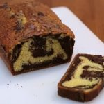 Marble cake sliced on a white cutting board