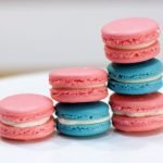 blue and pink classic French Macarons on a white cake stand