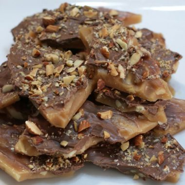 homemade almond roca piled up on a white plate