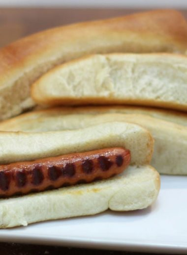 Homemade hot dog buns on a white plate on a wooden table