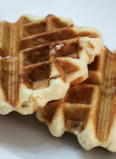Two belgian sugar waffles on a white plate on a wooden table