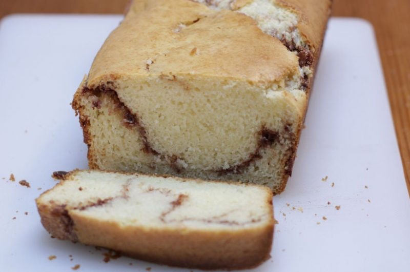 cinnamon quick bread sliced on a white cutting board