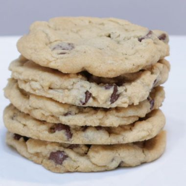 5 stacked eggless chocolate chip cookies on a white plate