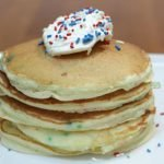 funfetti cake mix pancakes stacked on a white plate on a wooden table