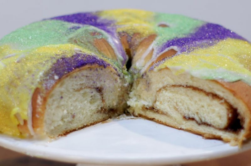 Mardi Gras king cake on a white cake pedestal on a wooden table