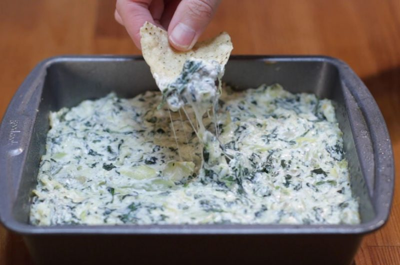 Spinach Artichoke dip in a square metal pan and hand dipping a chip in it.