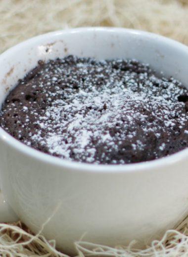 chocolate cake in a white mug with powdered sugar