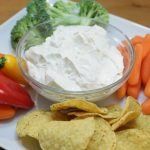 Creamy garlic dip on a white square plate with veggies and chips
