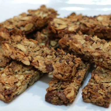 Keto granola bars piled up on a white plate
