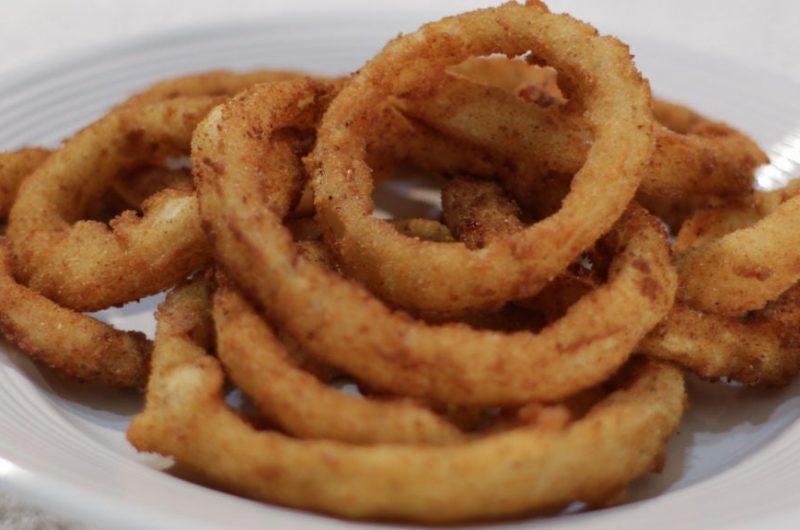 a pile of crispy onion rings on a white plate