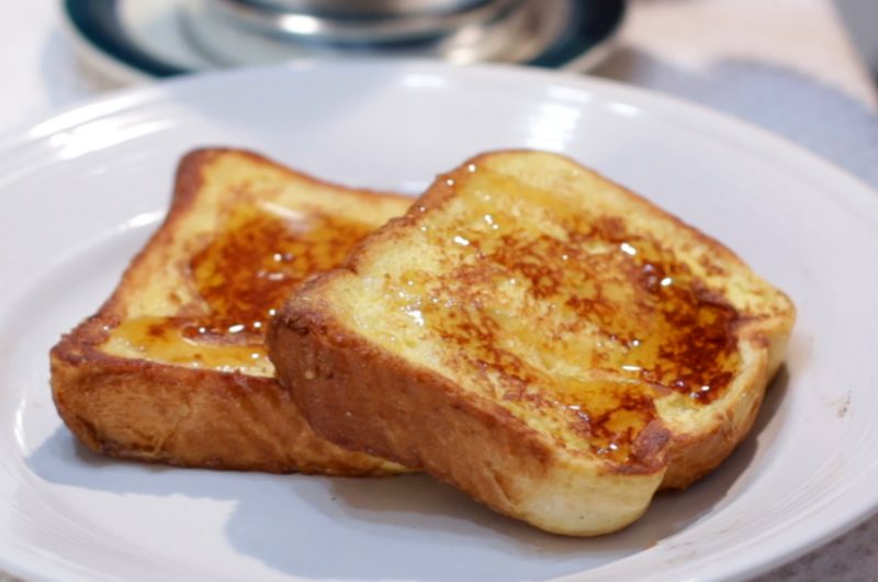2 slices of French toast on a white plate on a table.