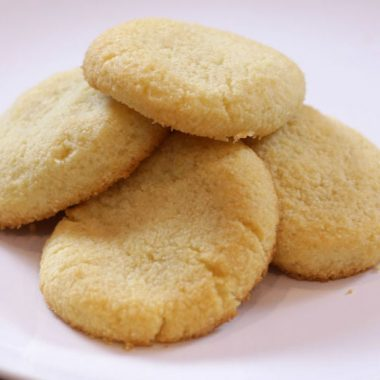 Keto shortbread cookies piled on a white plate.