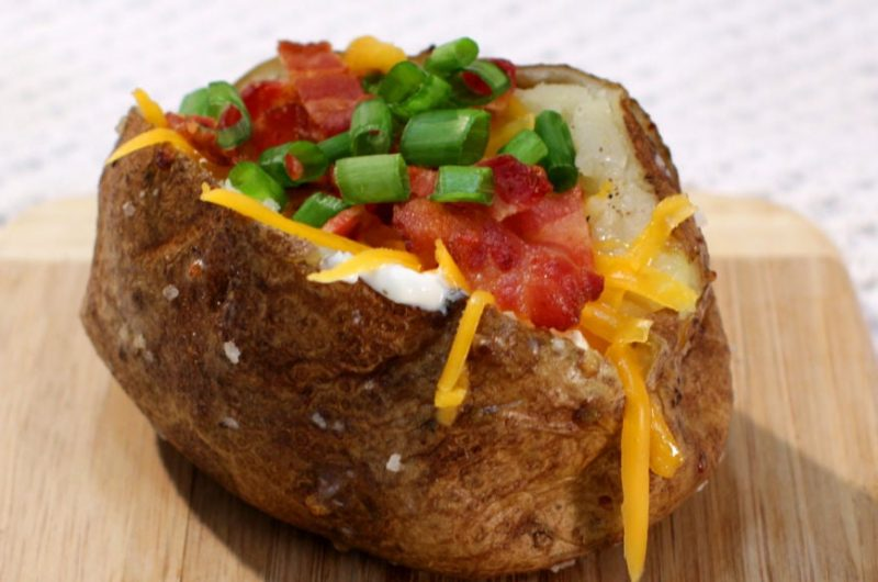 Perfect baked potato with green onion, bacon, cheese on a wooden cutting board.