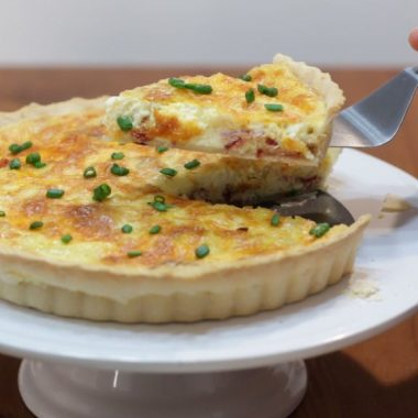 Bacon and cheese quiche in a tart pan on a white cake pedestal