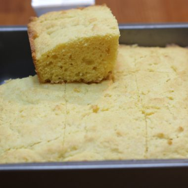 moist cornbread in a square metal pan on a wooden table