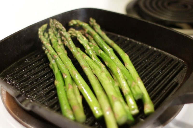 Grilled asparagus in a grill pan on a stove