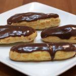 Four chocolate eclairs on a white plate on a wooden table.
