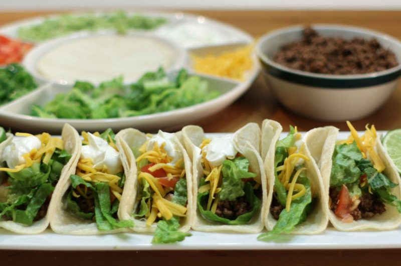 Ground beef tacos on a white plate on a wooden table