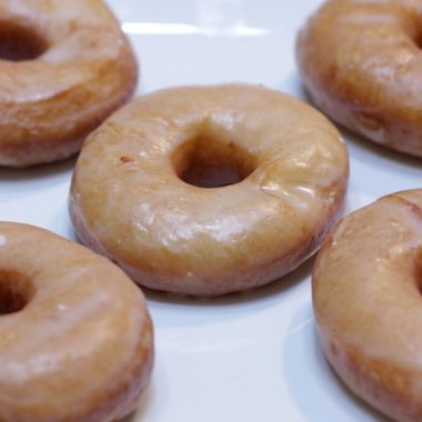 homemade glazed donuts on a white plate