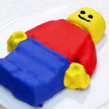 Lego man cake on a white pedestal