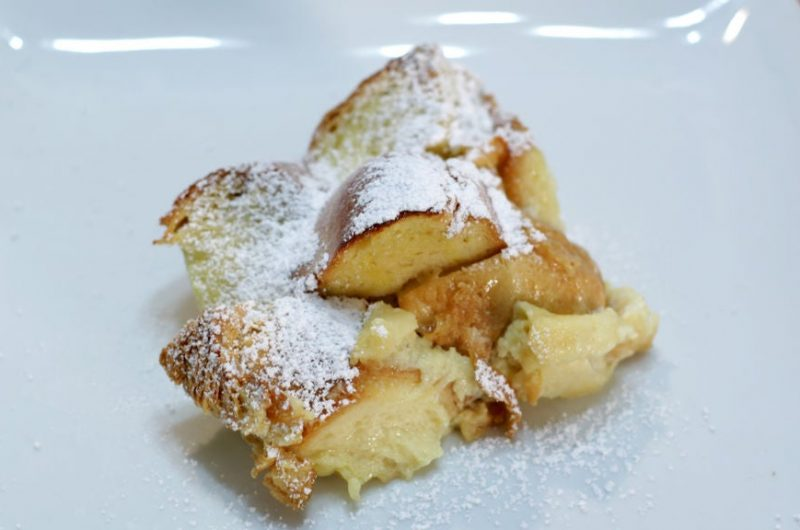 Homemade bread pudding topped with powdered sugar on a white plate
