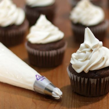 Easy homemade buttercream frosting on chocolate cupcakes and in a piping bag
