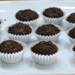 Homemade brigadeiro in a white paper cups on a white plate