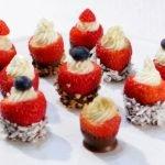 cheesecake stuffed chocolate dipped strawberries on a white cake pedestal.
