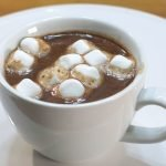 Homemade hot chocolate in a white mug on a white cake pedestal with marshmallows