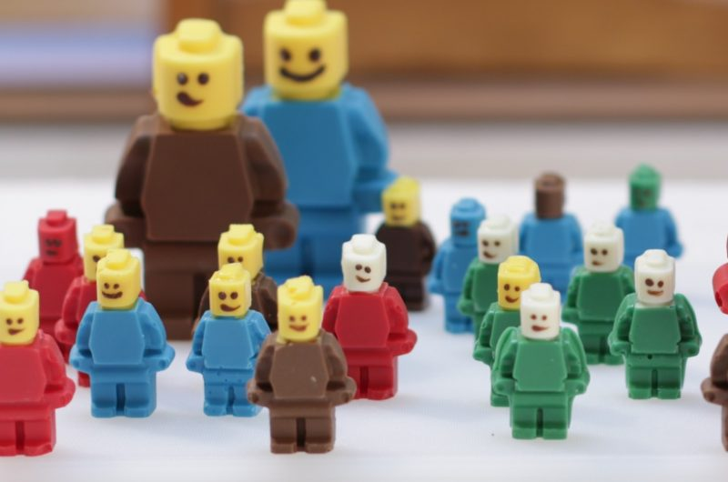 Several chocolate lego figures on a white table.