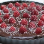 Chocolate raspberry tart on a white table