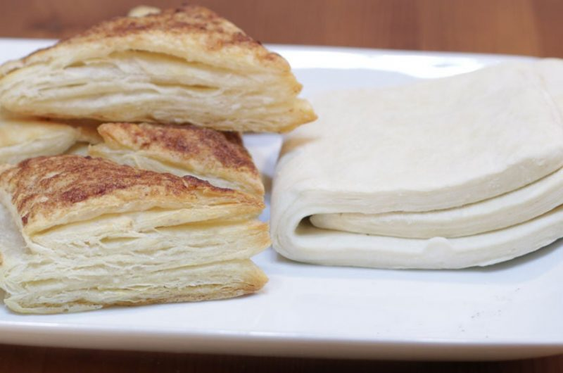 Homemade puff pastry dough folded next to cinnamon tarts