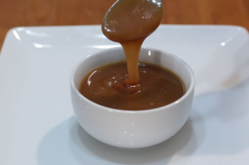 Homemade caramel sauce dripping off a spoon into a white bowl.