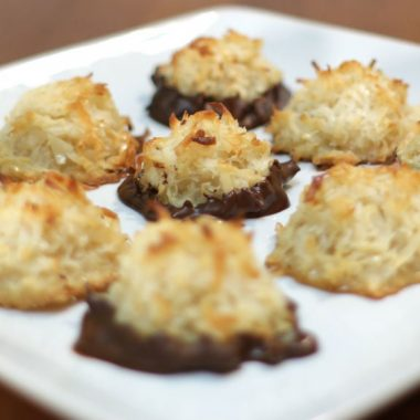 Coconut macaroons on a white plate on a wooden table.