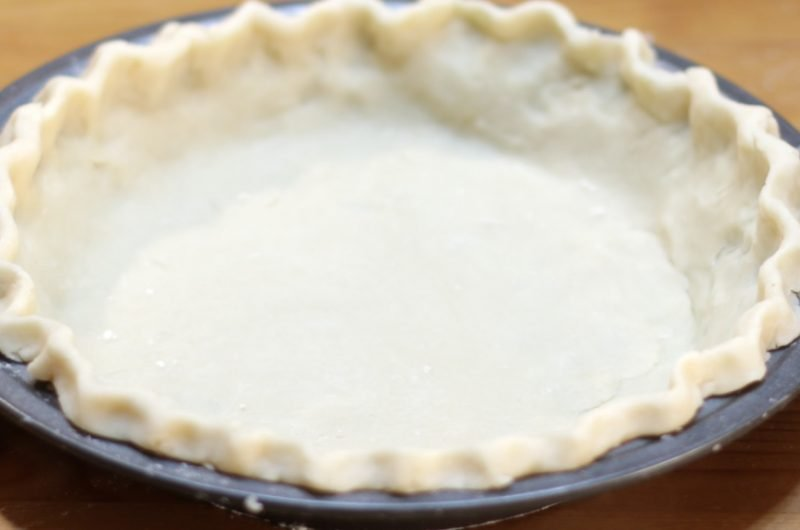 easy homemade perfect pie crust in metal pie plate on wooden table.