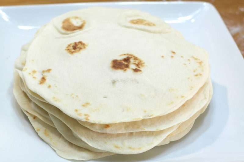 Homemade soft flour tortillas stacked on a white plate